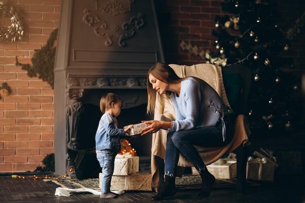 クリスマスツリーで椅子に座っている娘を持つ母