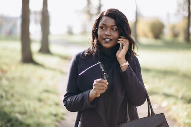 アフリカ系アメリカ人の女性が公園で電話で話しています。