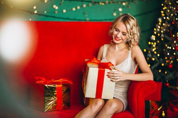Молодая женщина в платье с рождественскими подарками, сидя на диване