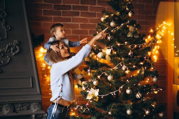 クリスマスツリーを飾る小さな娘を持つ母
