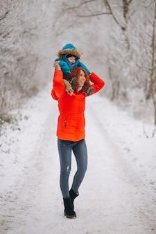 冬の公園で一緒に彼女の幼い息子を持つ母