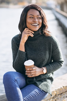 湖のそばでコーヒーを飲む若いアフリカ系アメリカ人女性