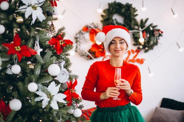 Женщина пьет шампанское у елки