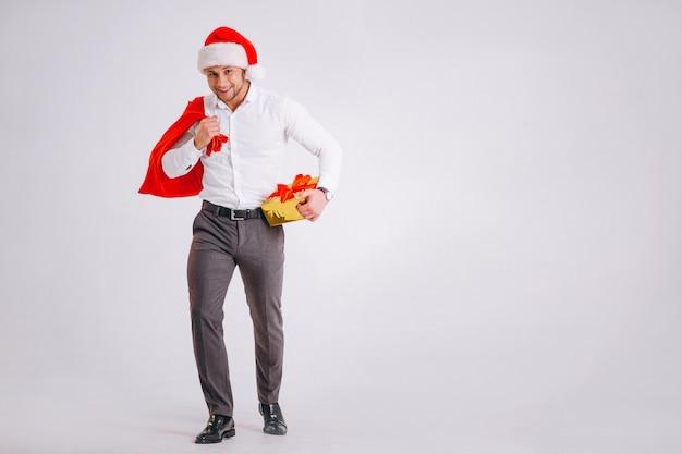 分離されたクリスマスプレゼントを持ってサンタ帽子のビジネスマン