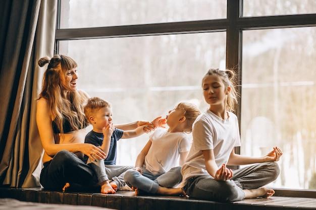 窓際に座っている子供たちと妊娠中の女性