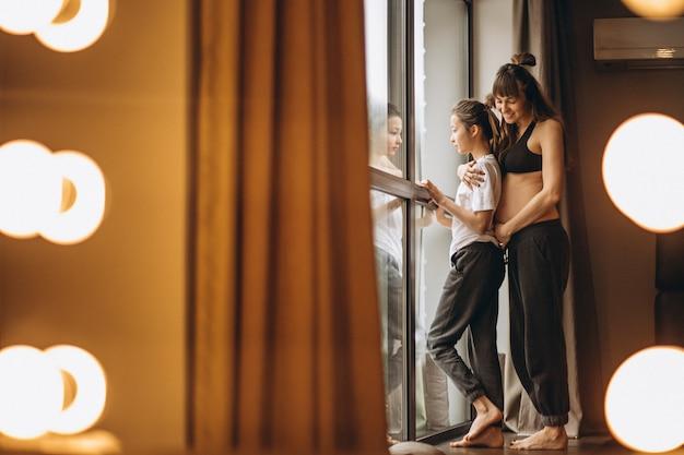 窓際に娘と一緒に立っている妊娠中の女性