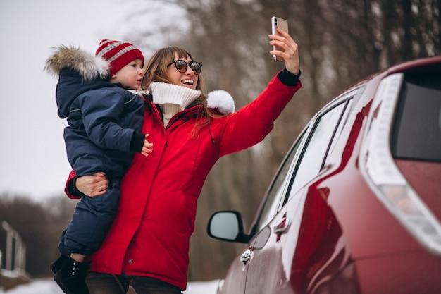 車で立っている息子を持つ母