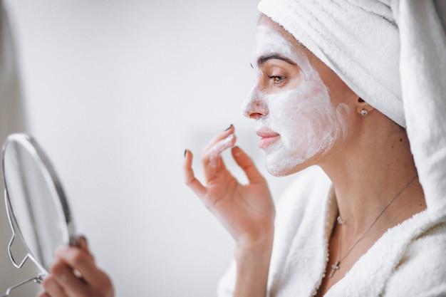 Женщина прикладывая маску красотки