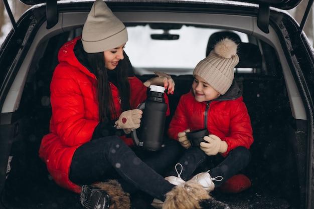 冬に車に座っている娘を持つ母