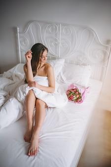 ベッドの中で花の花束を持つ女性