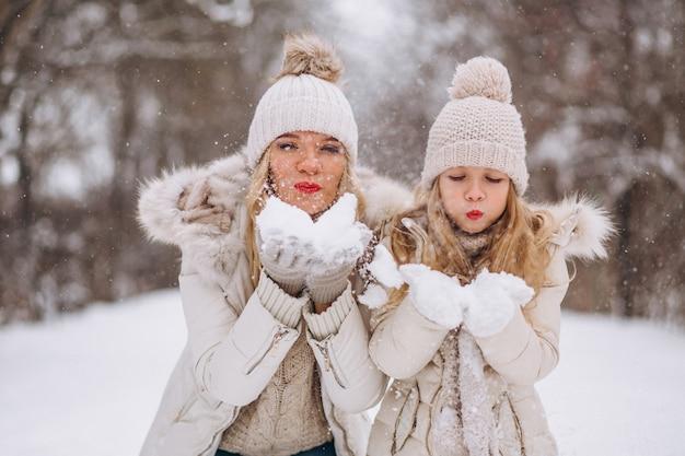 冬の公園で一緒に歩いている娘を持つ母