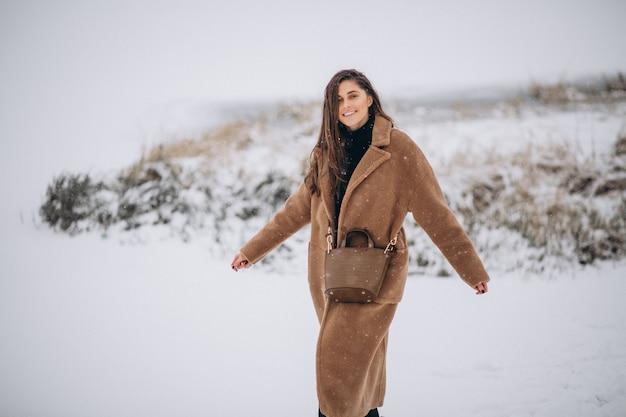 公園の外の冬のコートで幸せな女