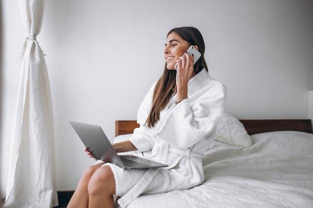 若い女性がベッドの中でコンピューターに取り組んで