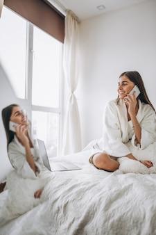 ベッドの中でコンピューターで作業して電話で話している女性
