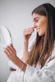 パッドと化粧を削除する鏡を持つ女性
