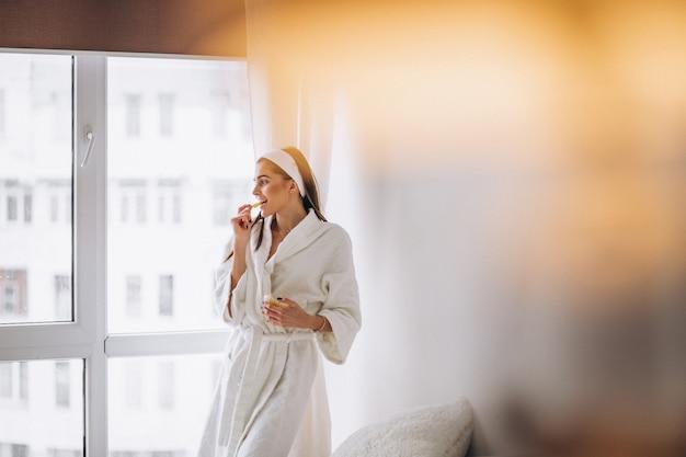 窓のそばに立って、シリアルを食べるバスローブの女