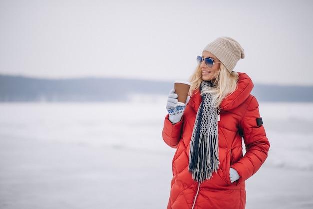 冬の外のコーヒーを飲む女性