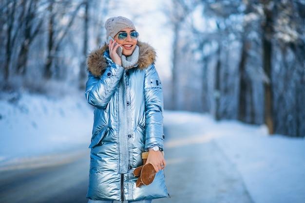 Женщина в зимнем парке разговаривает по телефону