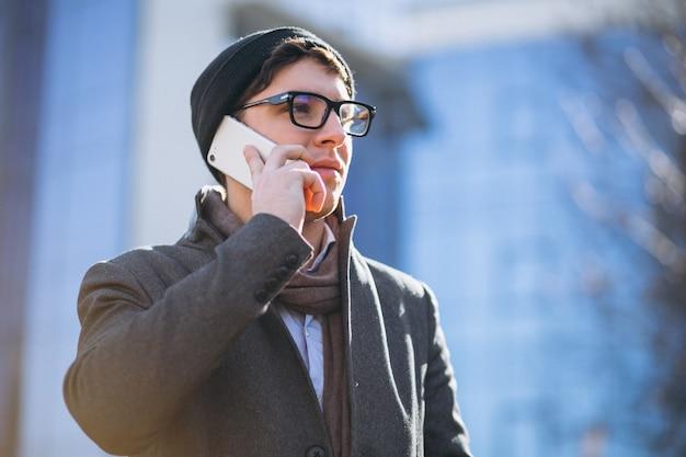 電話を使用して高層ビルのビジネスマン