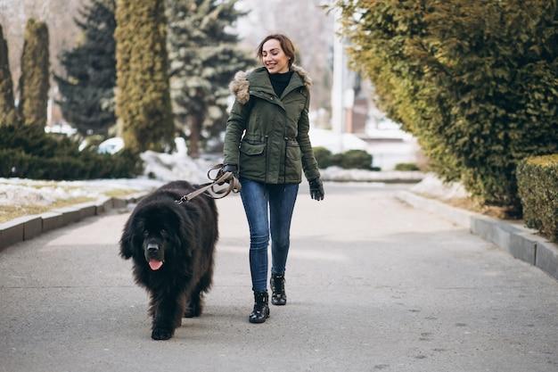 公園を歩いて彼女の犬を持つ女性
