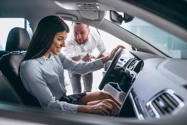 Продавец и женщина ищут машину в автосалоне