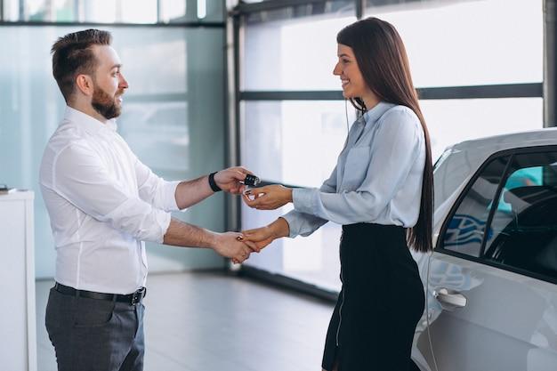 セールスマンと車のショールームで車を探している女性