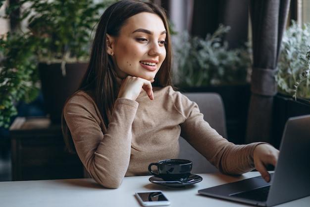 ビジネスの女性がコーヒーを飲むと、カフェでのラップトップに取り組んで