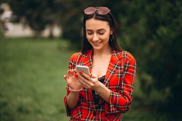 Молодая женщина с помощью телефона