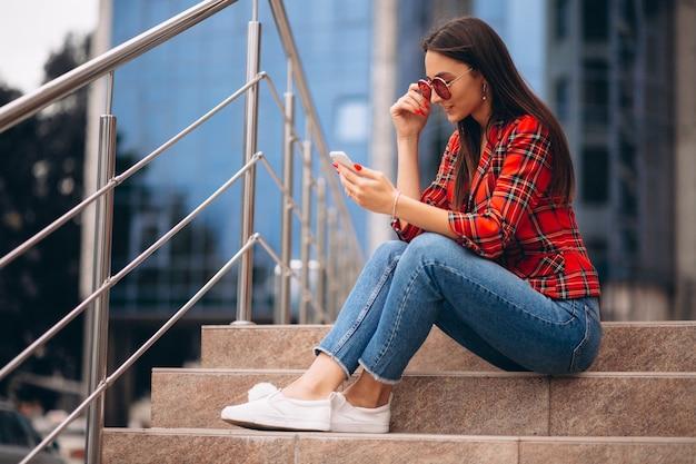階段の上に座っていると電話で話している若い女性