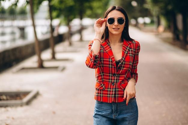 Милая женщина в красной куртке снаружи в парке