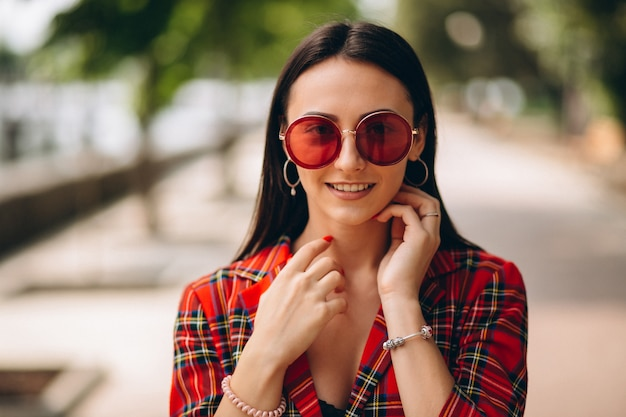 Портрет молодой леди в красной куртке и красных очках