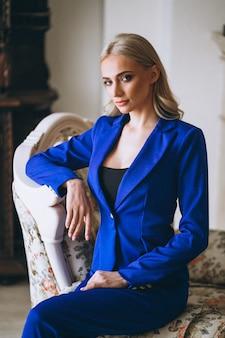 窓のそばに立っている青いスーツのビジネスウーマン