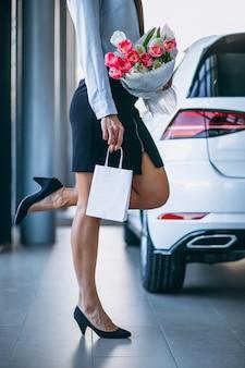 車のショールームで花を持つ女性