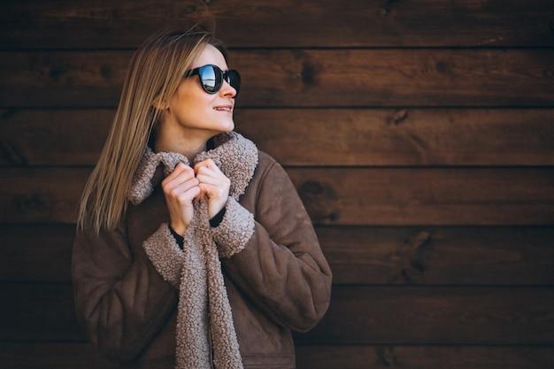 木製の背景の外の女性