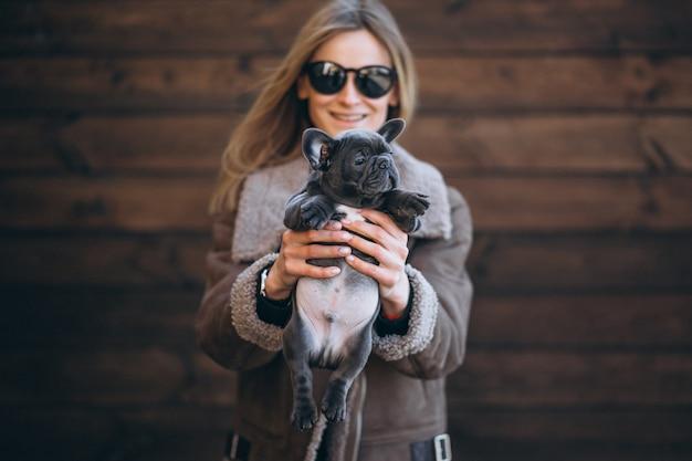 木製の背景に彼女のペットフレンチブルドッグを持つ女性