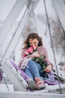 ブランコに座っている冬の外のバラを持つ女性