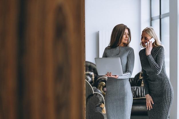 Два деловая женщина с компьютером