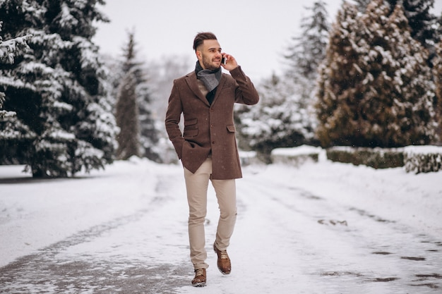 冬の公園で電話で話しているハンサムな男