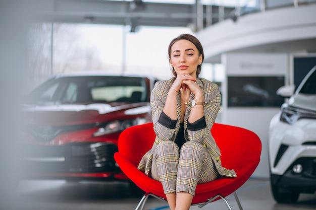 Женский босс на автосалоне сидит в красном кресле