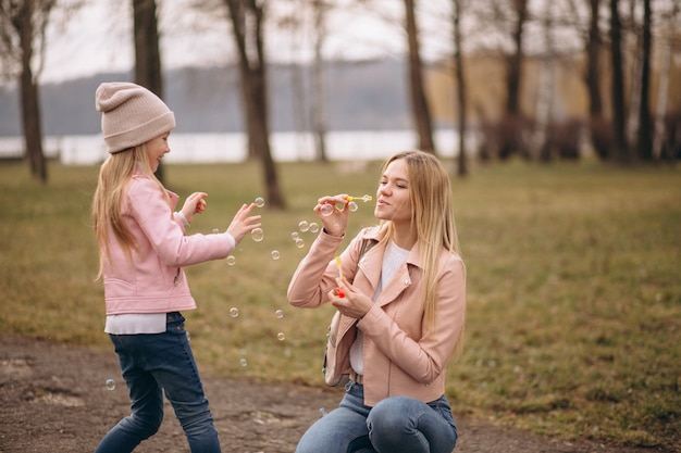 Мать с маленькой дочерью пускает мыльные пузыри