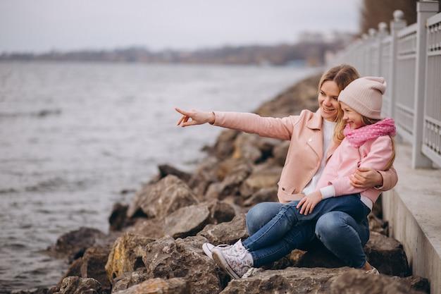 湖のそばに座って娘を持つ母