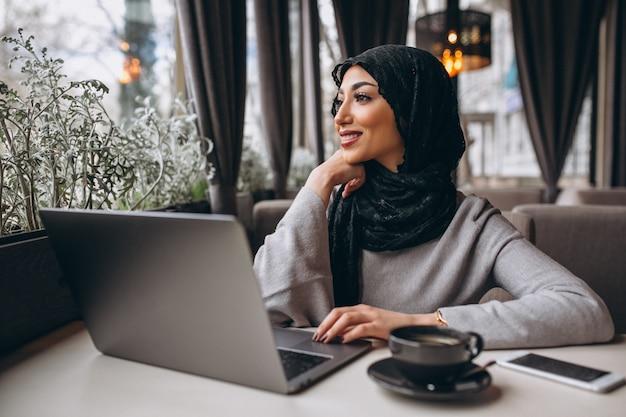 ラップトップに取り組んでいるカフェの中のヒジャーブのアラビア女性