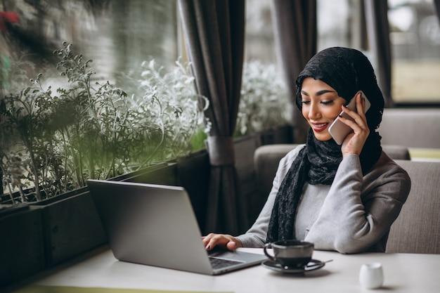Арабская женщина в хиджабе в кафе работает на ноутбуке