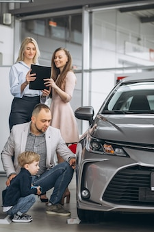 Семья с сыном, выбирая автомобиль в автосалоне