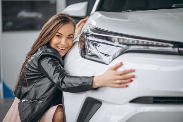美しい女性が車を抱き締める