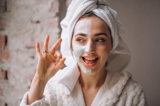 顔のマスクの半分の顔を持つ女性の肖像画