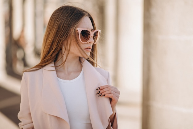 通りを歩いてコートを着た女性