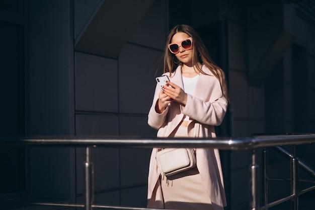 Женщина в пальто гуляет на улице и разговаривает по телефону