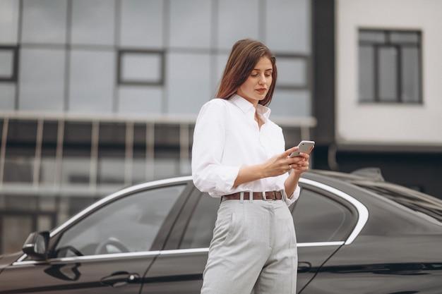 Деловая женщина, стоя у машины и с помощью телефона