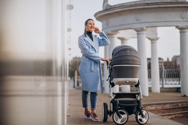 ベビーカーを公園で歩く若い母親